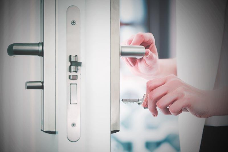 Schlüssel der in eine geöffnete Tür gesteckt wird.
