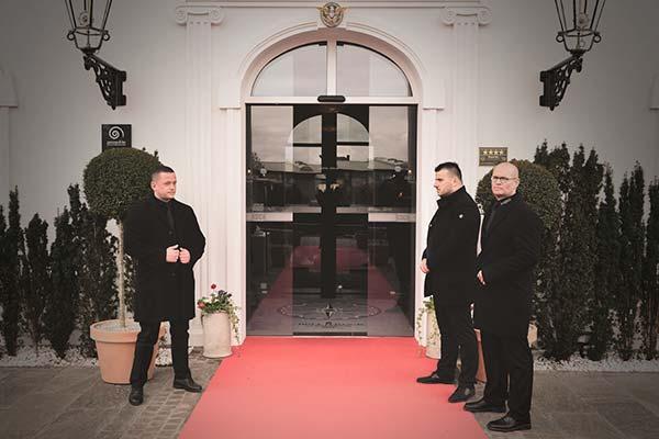 Patronus Mitarbeiter stehen auf einem Roten Teppich vor dem Eingang eines Hotels