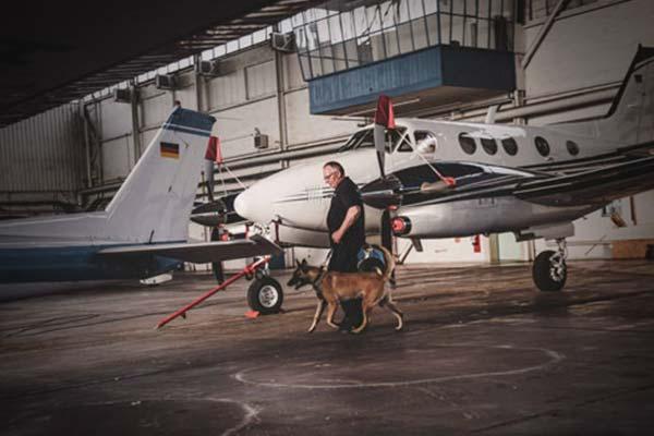 Ein Patronus Mitarbeiter läuft mit einem Hund durch einen Flugzeughangar